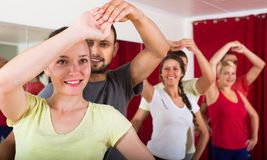 Adults dancing in dance studio. Smiling adults dancing a bachata together in dance studio royalty free stock image
