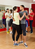Adults dancing in dance studio. Smiling adults dancing bachata together in a dance studio royalty free stock photos