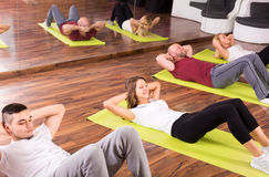 Adults doing abs. Adults at a fitness school indoor are doing abs Stock Images