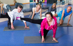 Adults doing pilates routine. Group of active adults doing pilates routine in a sport club Royalty Free Stock Photography
