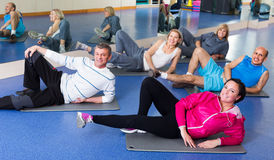 Adults doing pilates routine. Group of happy active adults doing pilates routine in a sport club Royalty Free Stock Photos