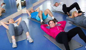 Adults doing pilates routine. Group of adults doing pilates routine in a sport club Royalty Free Stock Photo