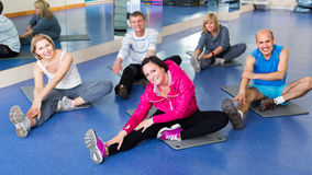 Adults doing pilates routine. Mature active adults doing pilates routine in a sport club Stock Images