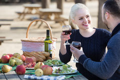 Adults drinking wine at table. Portrait of young caucasian adults drinking wine at table in nature Stock Images