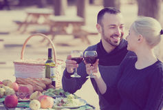 Adults drinking wine at table. Portrait of young adults drinking wine at table in nature  together Royalty Free Stock Photo