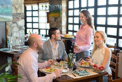 Adults eating out in restaurant. Happy adults eating out in a fashionable restaurant while young and beautiful waitress is serving them Royalty Free Stock Photo