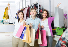 Adults in good mood holding bags at clothing store Royalty Free Stock Photos