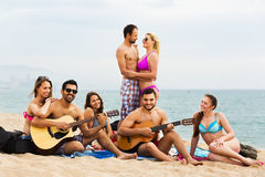 Adults with guitar at beach Stock Images