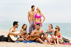 Adults with guitar at beach. Positive adults with guitar relaxing at sandy beach in a summer day Royalty Free Stock Image