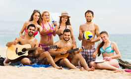 Adults with guitar at beach. Positive adults with guitar relaxing at a sandy beach in summer day Stock Photo