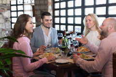 Adults having dinner in restaurant. Portrait of happy adults having dinner in family restaurant Stock Image