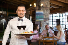 Adults having dinner and waiter Royalty Free Stock Image