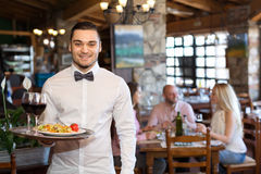 Adults having dinner and waiter Royalty Free Stock Images