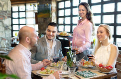Adults having dinner and waiter. Portrait of cheerful adults people having dinner and respectful waiter royalty free stock photo