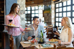 Adults having dinner and waiter. Portrait of smiling  adults people having dinner and respectful waiter Royalty Free Stock Photography