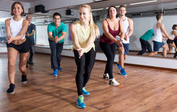 Adults having group fitness class. Smiling adults having group fitness class in sport club Royalty Free Stock Image