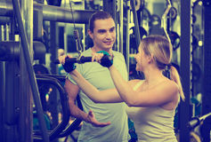 Adults having strength training. Positive active adults people having strength training under coach control in gym Royalty Free Stock Image
