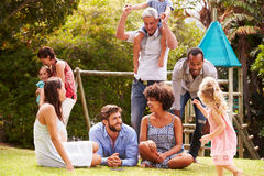 Adults and kids having fun in a garden Stock Images
