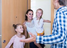 Adults and kids meeting at doorway and greeting one another Stock Images