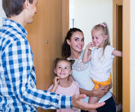 Adults and kids meeting at doorway and greeting one another Stock Image