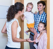 Adults and kids meeting at doorway and greeting one another Stock Photo