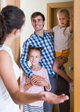 Adults and kids meeting at doorway and greeting one another Royalty Free Stock Photos