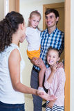 Adults and kids meeting at doorway and greeting one another Royalty Free Stock Images