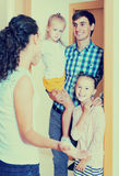 Adults and kids meeting at doorway and greeting one another Stock Photos