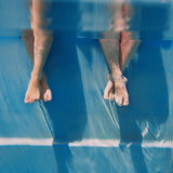 Adults legs underwater in the swimming pool Royalty Free Stock Photo