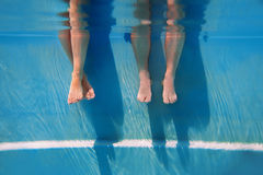 Adults legs underwater in the swimming pool. In summer Stock Image