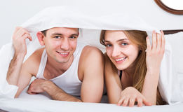 Adults lying under sheet Royalty Free Stock Images