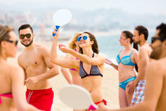 Adults playing paddle games on beach Royalty Free Stock Images