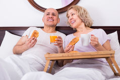 Adults posing with coffee and pastry Royalty Free Stock Image