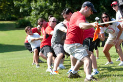 Adults Pull Rope In Team Tug-Of-War Competition Stock Images