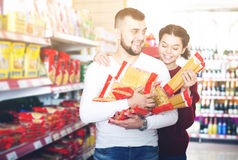 Adults reading lable of pasta. Smiling adults reading lable of pasta at supermarket Stock Photo