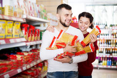 Adults reading lable of pasta. Smiling adults reading lable of pasta at supermarket Royalty Free Stock Photo