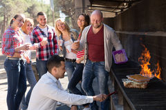 Adults relaxing at grill party Stock Photography