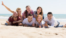 Adults relaxing at sandy beach Stock Photos