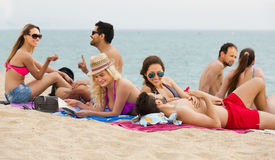 Adults relaxing at sandy beach Royalty Free Stock Photos