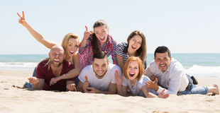Adults relaxing at sandy beach Royalty Free Stock Image