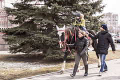 Adults ride with a child on horseback in a park at Carnival stock photography