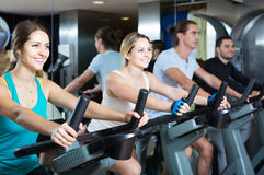 Adults riding stationary bicycles in fitness club Stock Image
