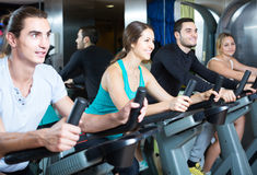 Adults riding stationary bicycles in fitness club Stock Photo