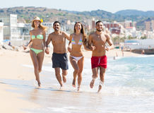 Adults running at sandy beach Stock Photo