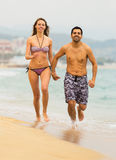 Adults running in swimwear on the sea waves Royalty Free Stock Photos