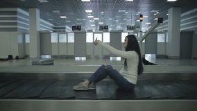Adults sitting on the moving luggage belt in the airport. The arriving hall of the airport, the baggage claim desk. People sit at the luggage belt and move along stock footage