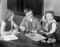 Adults testing little boy doing puzzle Royalty Free Stock Photos