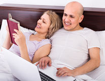 Adults together reading news from notebook and smartphone  in be Royalty Free Stock Photos