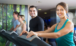 Adults training on treadmills. Happy group of adults training on treadmills in gym Stock Images