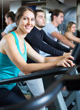 Adults training on treadmills. Happy group of adults people training on treadmills in gym Stock Photography
